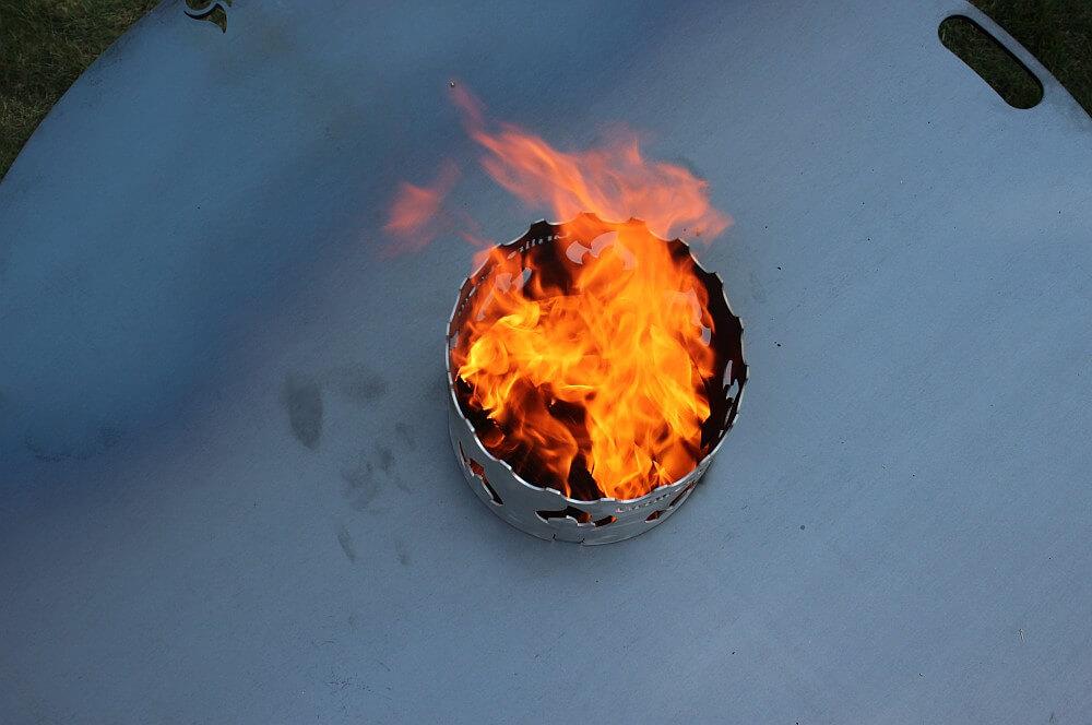 Die Flammen lodern aus der XXL-Feuerplatte xxl-feuerplatte-XXL Feuerplatte Grillrost com 100cm Durchmesser 07-XXL-Feuerplatte von Grillrost.com mit 100 cm Durchmesser